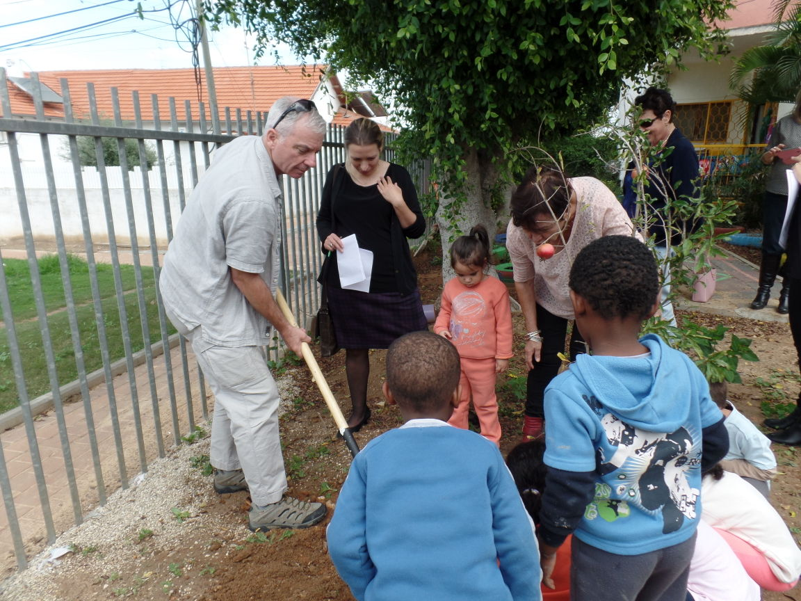 Jim Hartnett, director of community-wide security for the Jewish Federation of Cleveland, helps to plant a tree at a school in Beit Shean, Cleveland's sister city in Israel.